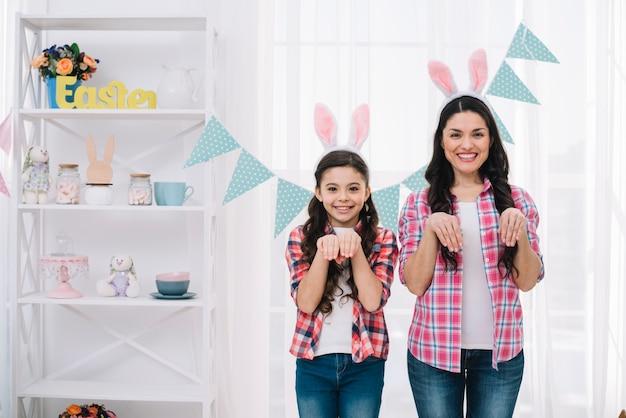 집에서 토끼처럼 포즈 부활절 토끼 귀를 입고 어머니와 딸의 초상화
