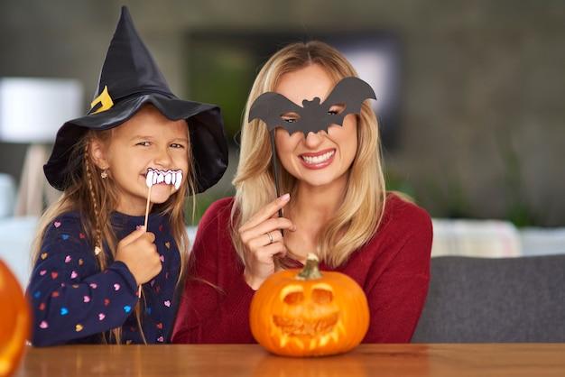 ハロウィーンのマスクを持つ母と娘の肖像画