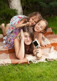 Портрет матери и дочерей, делающих фотографии на камеру в парке