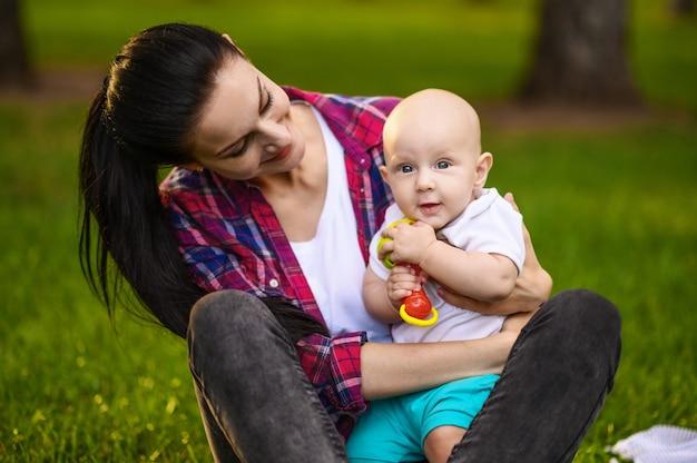 어머니와 그녀의 작은 아기의 초상화는 여름 공원에서 잔디에 앉아있다