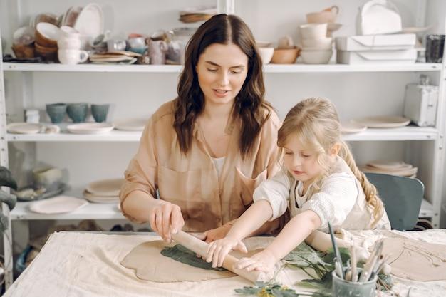 Портрет матери и маленькой девочки, образующей глину вместе