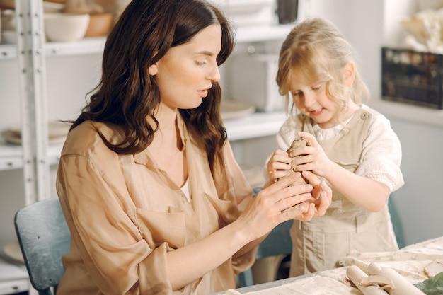 어머니와 함께 점토를 형성하는 어린 소녀의 초상화