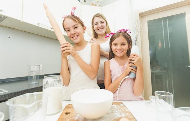 요리하는 동안 부엌에 포즈 어머니와 두 딸의 초상화
