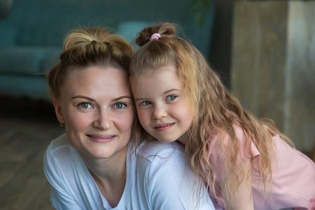 Портрет матери и дочери в спортивной одежде, обниматься и смотреть в камеру.