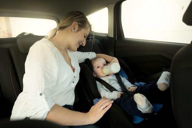 자동차 안전 좌석에 아기를 먹이는 어머니의 초상화