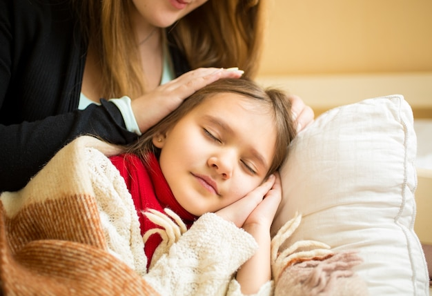 眠っている娘の頭に手をつないでいる母親の肖像画