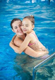 スイミング プールで娘を抱き締める母親の肖像画