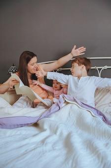 ベッドに座っている娘と息子の子供たちに物語の本を読んでいる母親の肖像画。週末の家族の余暇の時間の概念。