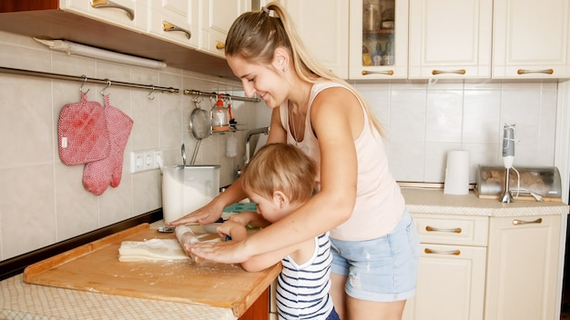 Портрет матери с сыном малыша 3 лет выпечки печенья на кухне утром. счастливая семья, выпечка и приготовление еды дома