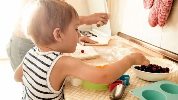 아침에 부엌에서 쿠키를 굽고 있는 3살짜리 아들을 둔 어머니의 초상화. 집에서 베이킹과 요리를 하는 행복한 가족