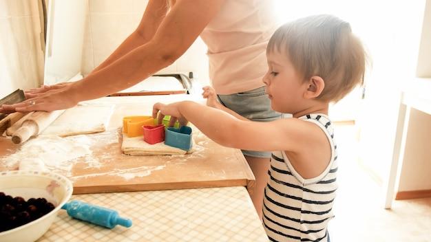 朝のキッチンでクッキーを焼く3歳の幼児の息子を持つ母親の肖像画。幸せな家族が家で焼いて料理する