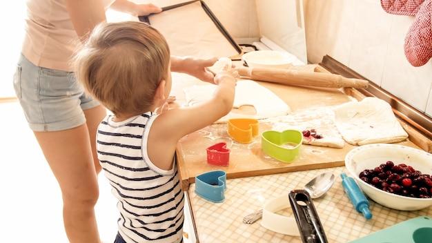 아침에 부엌에서 쿠키를 굽고 3 년 유아 아들과 어머니의 초상화