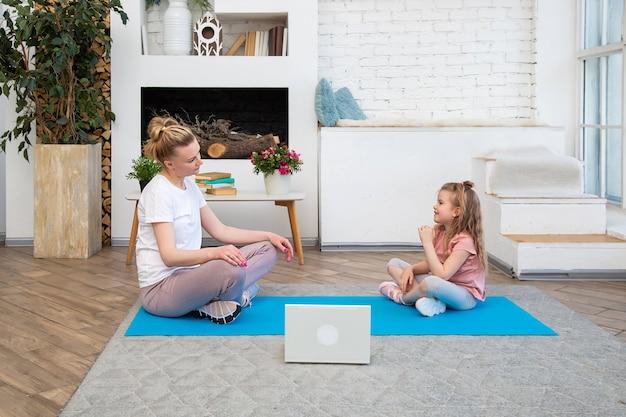Портрет матери с дочерью, занимающейся йогой онлайн, используя ноутбук, сидя в позе лотоса на коврике