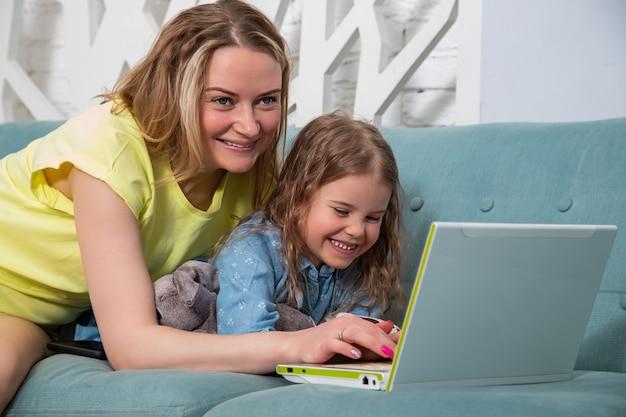 노트북과 함께 소파에 누워 딸과 함께 어머니의 초상화와 미소로 모니터를 봐.
