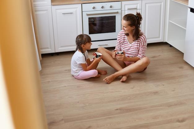 Портрет матери с маленькой дочерью, сидящей на полу на кухне и пьющей кофе или чай, маленькая девочка, рассказывающая секреты маме, семья счастлива проводить время вместе.