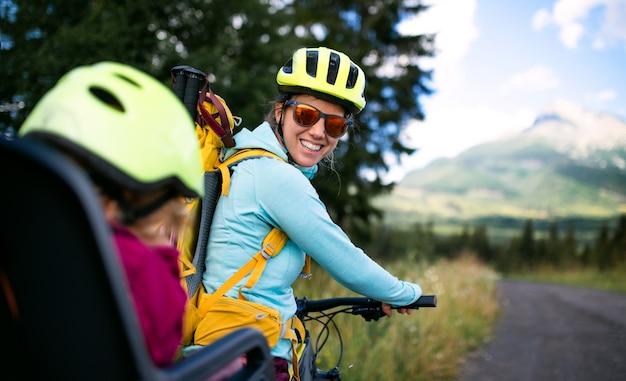 カメラを見て、夏の自然の中で屋外でサイクリングする小さな娘を持つ母親の肖像画。