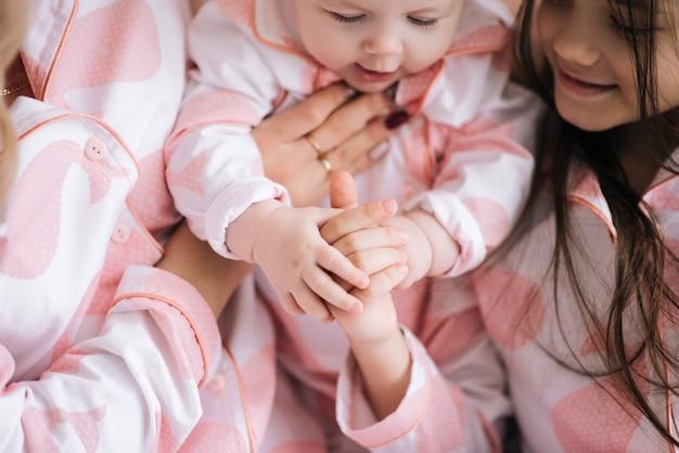 同じピンクのパジャマ、家族の顔の白い部屋で2人の娘を持つ母の肖像画