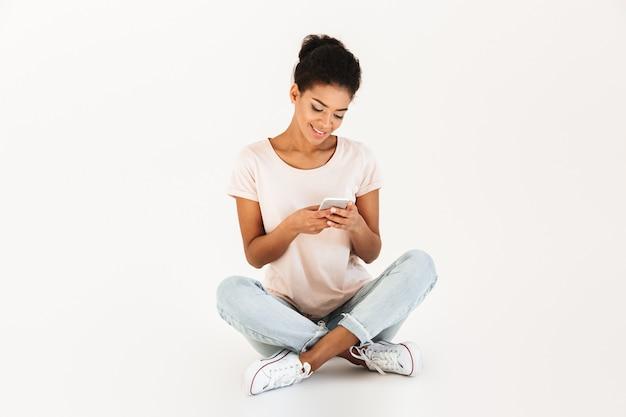 Портрет женщины мулата в случайных сидя на полу со скрещенными ногами и с помощью мобильного телефона, изолированных на белой стене