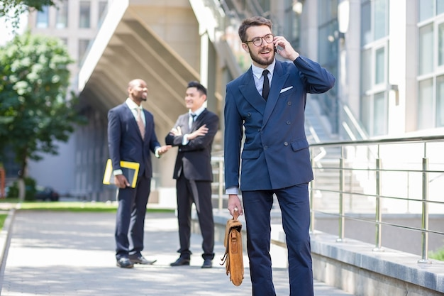 Портрет многоэтнической бизнес-команды. трое мужчин, стоящих на фоне города. на переднем плане мужчина из европы разговаривает по телефону. остальные мужчины - китайцы и афроамериканцы.