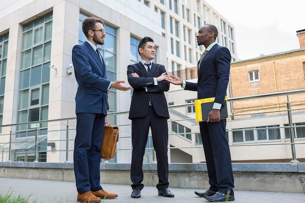 Портрет многоэтнической бизнес-команды. три улыбающихся человека, стоящих на фоне города. один мужчина - европеец, другой - китаец и афроамериканец.