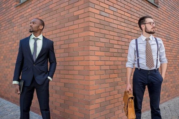 多民族のビジネスチームの肖像画。街を背景に立っている二人の男。一人はアフリカ系アメリカ人、もう一人はヨーロッパ人です。ビジネスの成功の概念
