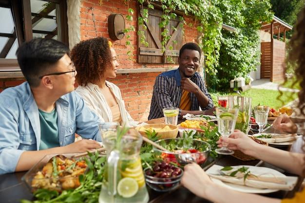 オープンテラスのテーブルに座って屋外で一緒に夕食を楽しんでいる友人の多民族グループの肖像画、物語を共有するアフリカ系アメリカ人の男性の笑顔に焦点を当てる