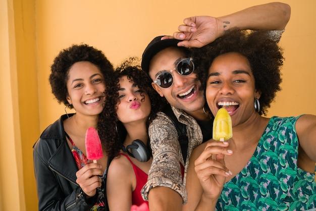 黄色の背景にアイスクリームを食べながら夏を楽しんで楽しんでいる友人の多民族グループの肖像画。