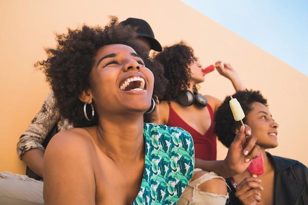 アイスクリームを食べながら夏を楽しんで楽しんでいる友人の多民族グループの肖像画。