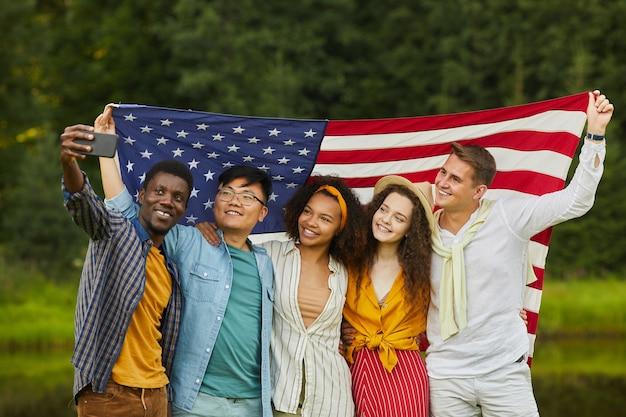 Портрет многонациональной группы друзей, держащих американский флаг и делающих селфи на открытом воздухе, наслаждаясь вечеринкой летом