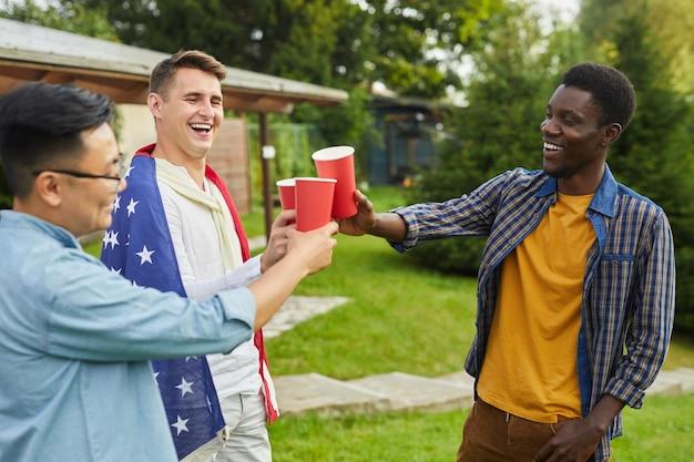 Портрет многонациональной группы мужчин, пьющих пиво во время вечеринки на открытом воздухе летом в день независимости