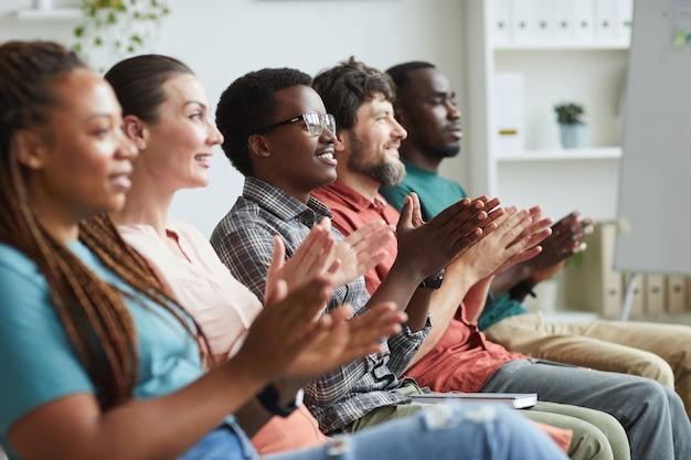 Портрет многонациональной группы людей, аплодирующих сидя в ряду в аудитории или конференц-зале