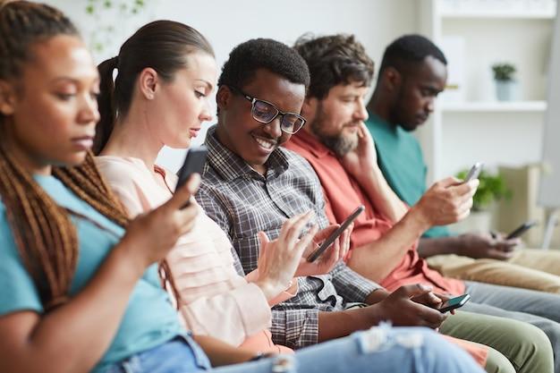 Портрет многоэтнической группы людей, сидящих в ряду и использующих смартфоны в ожидании конференции, сосредоточен на улыбающемся афроамериканском мужчине, разговаривающем с коллегой рядом с ним