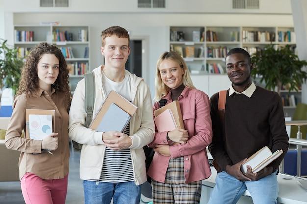 학생들의 다민족 그룹의 초상화와 대학 도서관에 서있는 동안 웃고