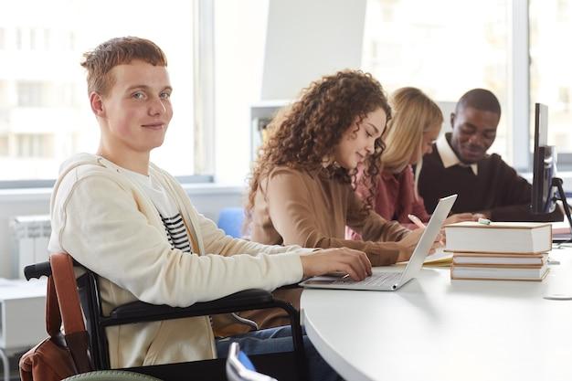 大学で勉強中にラップトップを使用している学生の多民族グループの肖像画、車椅子を使用して陽気な男の子をフィーチャー