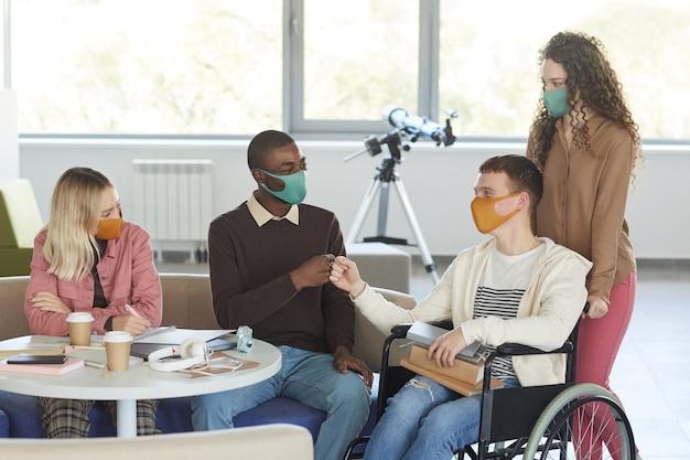 Портрет многонациональной группы студентов в масках во время обучения в библиотеке колледжа с молодым человеком, использующим инвалидную коляску на переднем плане,