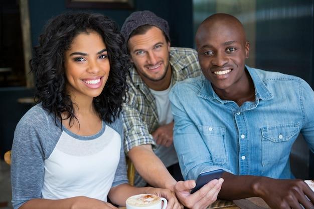 Портрет многоэтнических друзей мужского и женского пола с мобильным телефоном в кафе