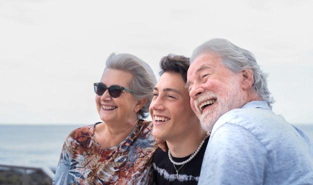 Портрет семьи из нескольких поколений, обнимающейся, счастливо улыбаясь, стоящей на открытом воздухе у моря