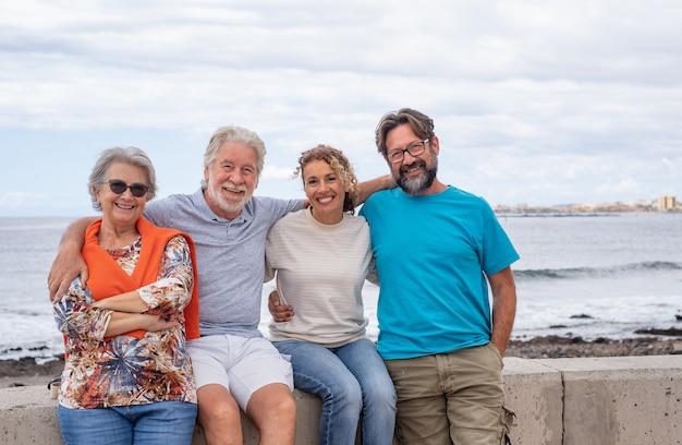 Портрет семьи из нескольких поколений, сидящей на берегу моря, улыбаясь, обнимая друг друга