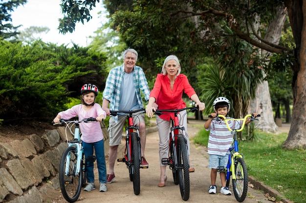 Портрет семьи нескольких поколений стоя с велосипедом в парке