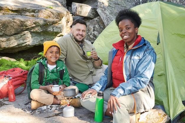Портрет многонациональной семьи туристов, улыбаясь в камеру, сидя на открытом воздухе и попивая чай