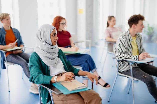실내 교실에 앉아 공부하는 다민족 대학생들의 초상화.