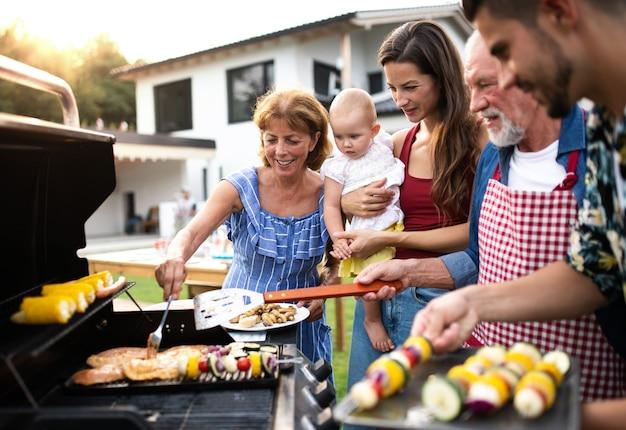 庭のバーベキュー、グリル、おしゃべりで屋外で多世代家族の肖像画。