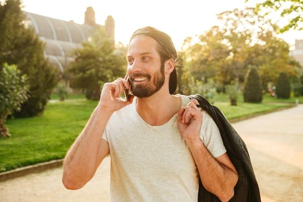 Портрет мускулистого привлекательного парня в кепке и белой футболке, держащего кожаную куртку на плече и говорящего по мобильному телефону, во время прогулки в зеленом парке