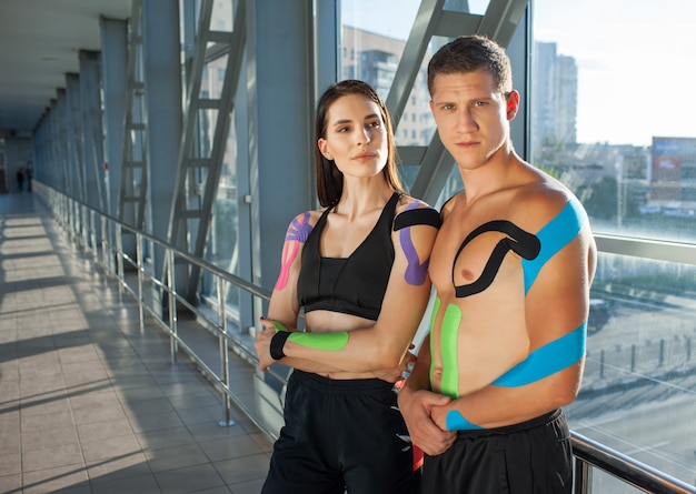 Портрет мускулистой женщины брюнет со скрещенными руками и мужчиной, смотрящим в камеру с сильным лицом. молодая пара спортсменов позирует в помещении, красочные кинезиотейпирования на теле, футуристический интерьер.