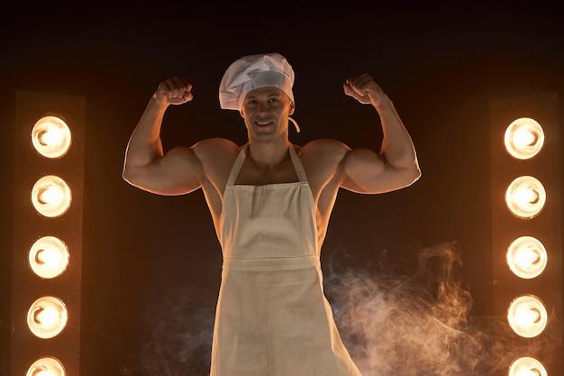 연기가 자욱한 배경 남성 주부에 강한 팔뚝 근육을 보여주는 흰색 앞치마와 요리사 모자를 쓰고 근육 요리사의 초상화. 부엌에서 남편. 잔인한 정육점.
