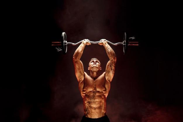 赤い煙でダンベルを持ち上げる筋肉の男の肖像画。スタジオショット。上腕三頭筋の運動