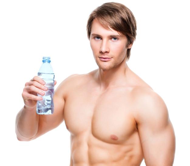 筋肉質の上半身裸のスポーツマンの肖像画は水を保持します-白い壁に隔離されます。