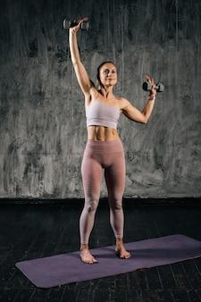 頭の上に2つのダンベルを持ち上げる筋肉の若い運動女性の肖像画。