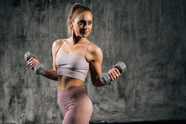 ウェイトリフティングと目をそらして運動をしているスポーツウェアを身に着けている完璧な美しい体を持つ筋肉の若い運動女性の肖像画。スタジオでポーズをとる白人フィットネス女性。