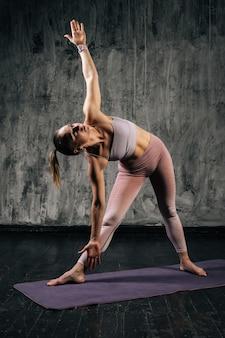 スポーツウェアを身に着けて、下を向いて目をそらしている完璧な美しい体を持つ筋肉質の若い運動女性の肖像画、濃い灰色の背景のスタジオでポーズをとっている白人フィットネス女性。